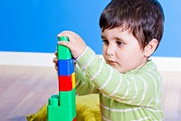 Brunette Baby playing with bright blocks on wooden room
