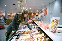 Tilburg, Netherlands. Young woman buying groceries in a supermarket.