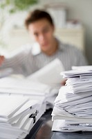 Stack of Documents, Businessman in Background
