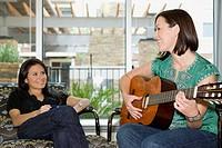 Woman Watching Friend Play Guitar