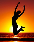 Silhouette of an energetic woman jumping on the beach at sunset