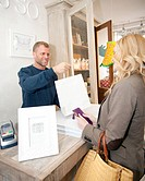 A male shop assistant handing purchases to a female customer