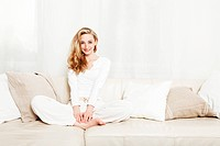 beautiful blond woman sitting on couch