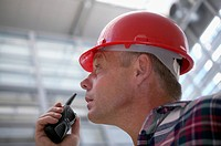 Low angle view of a construction worker using a walkie_talkie