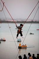 Boy swinging pole at Le Corbusier architectural wonder  ; Sukhna lake  ; Chandigarh Union Territory  ; India
