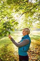 Woman admiring leaves in park