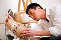 A male artist making pottery in studio