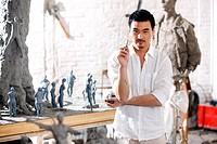 A male sculpturer sculpturing in studio