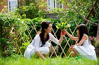 Oriental woman and daughter pulling radish outdoors