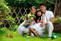 Oriental family on grass in front of fence holding vegetable