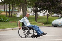 Man with spinal cord injury in a wheelchair crossing at accessible street walk