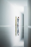 Businessman on cell phone in corridor
