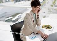 Businesswoman multitasking at desk