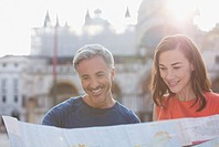 Smiling couple looking at map in Venice