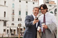 Smiling businessmen with coffee looking down at cell phone in Venice