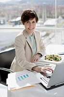 Portrait of smiling businesswoman eating lunch and working at desk
