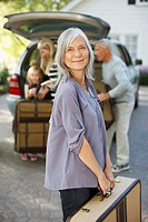 Woman carrying suitcase to trunk