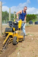 Young Caucasian man of 24 years is operating a walk-behind trencher to make a ditch for pipes and cable