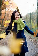 Woman playing in autumn leaves