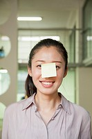 Chinese businesswoman with sticky note on nose