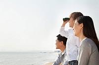 Chinese boy using binoculars on beach