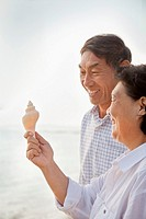 Older Chinese couple examining shell on beach