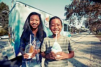 Mixed race children eating ice cream from truck