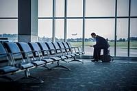 Caucasian businessman sitting suitcase in airport