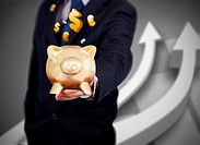 Businessman holding a gold piggy bank with currencies