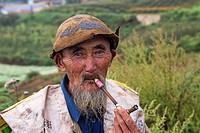 China, Yunnan Province, Kunming Municipality, Dongchuan District, Red lands, Xiguadi, man smoking, peasant shepherd