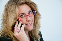 Young woman wearing spectacles, looking at the camera and using mobile phone. Close view.