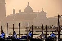 Gondolas at a dock in the Canal Grande. In front, the basilica di San Giorgio Maggiore in the isola di San Giorgio Maggiore. Venice, Veneto, Italy, Eu...