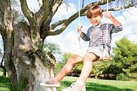 Cute boy on swing hanging from tree