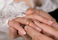 Man inserting wedding ring to wife, close up