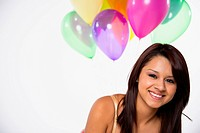 Portrait of young woman with balloons, smiling