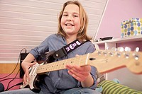 Girl playing guitar, smiling, portrait