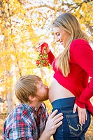 USA, Texas, Man kissing pregnant womans belly, close up