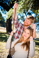 USA, Texas, Pregnant wife swinging while husband standing behind
