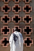 Man praying in front of a church wall in Addis Ababa, Ethiopia.