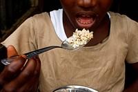 African girl eating rice, Togo.