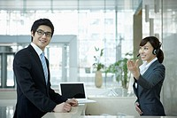 a businessman and help desk woman smiling at camera