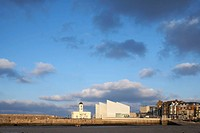 Turner Contemporary Gallery, Margate, United Kingdom. Architect: David Chipperfield Architects Ltd, 2011. Distant view across harbour with dramatic sk...