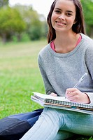Smiling student doing her homework while sitting on the grass