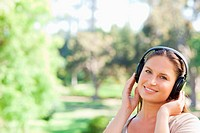 Smiling woman in the park listening to music