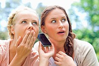 Friends listening to a phone call in the park