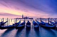 Venetian gondolas in the foreground with the church of San Giorgio Maggiore in the background at sunrise
