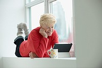 Caucasian woman using tablet computer in window