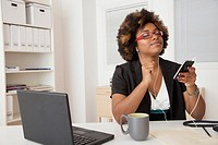 African American businesswoman listening to headphones at desk