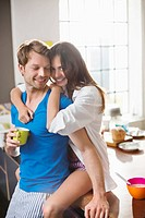 Smiling couple hugging in kitchen