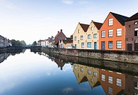Houses reflected in still urban canal